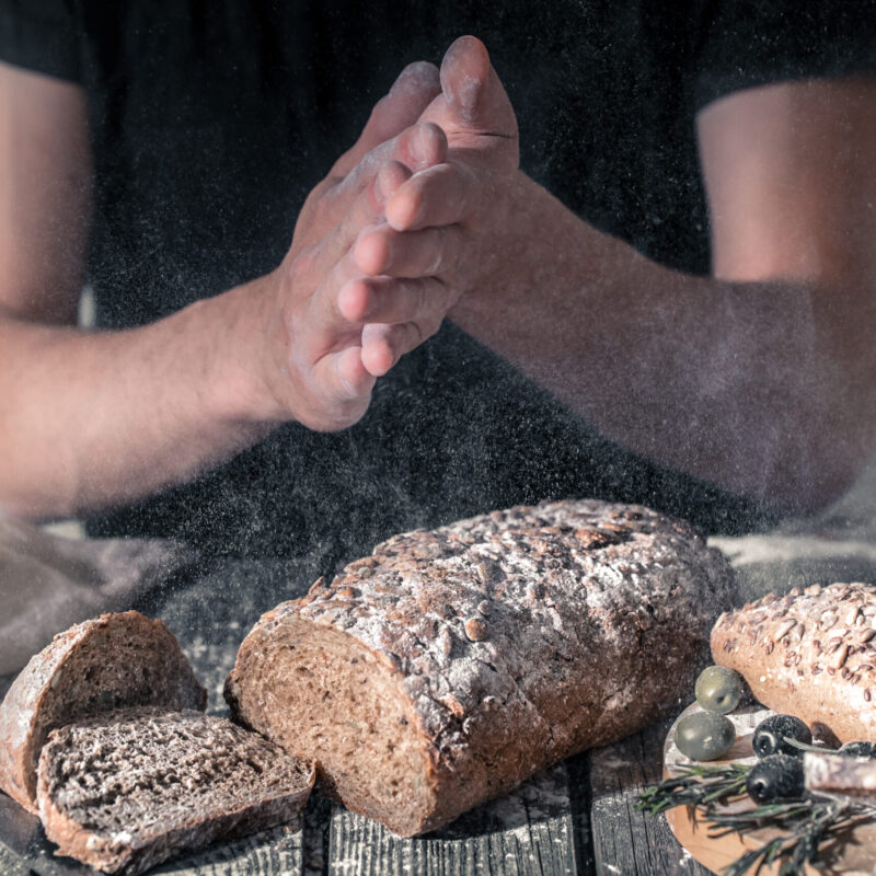 baker with flour in his hand and fresh bread on a beautiful wooden background, the concept of healthy food and bakery industry